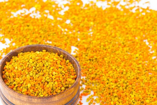 Цветочная пыльца в деревянном ящике. на белом рассыпана пыльца разного цвета