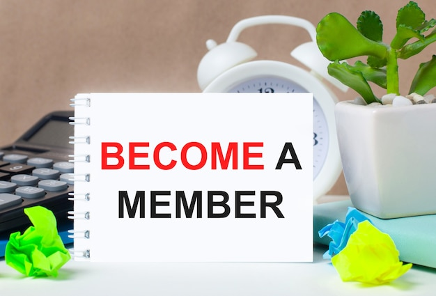 Flower in a pot, calculator, white alarm clock, multi-colored pieces of paper and a white notebook with the text become a member on the desktop.