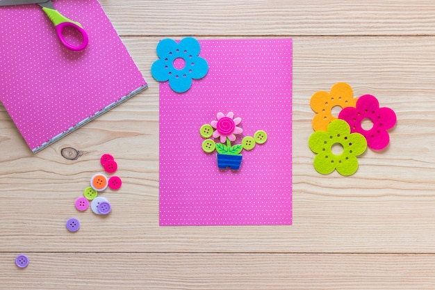 Flower pot decorated on pink card over the wooden table