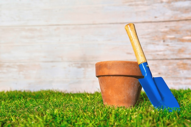 Flower pot empty with blue shovel in fresh green grass with wooden background texture, garden,spring,hobby,potting concept copy space bright colors