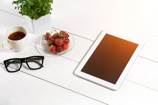 Flower pot, glasses, tablet on white desktop. white background. top view. copy space. sun flare