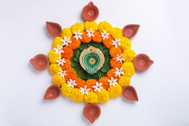 Flower rangoli for diwali festival made using marigold and leaf and oil lamp over white background
