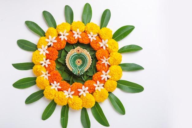 Цветок ранголи для фестиваля дивали из календулы и листьев и масляной лампы на белом фоне