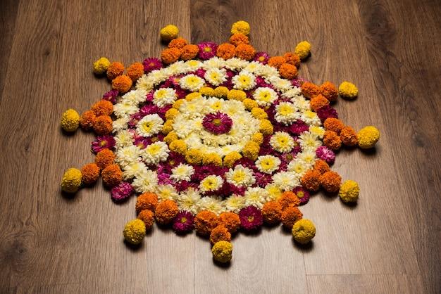 Diwali 또는 pongal festival을 위한 꽃 랑골리(flower rangoli)는 마리골드(marigold) 또는 젠두(zendu) 꽃과 장미 꽃잎을 변덕스럽거나 흰색 배경 위에 사용하여 만든 선택적 초점