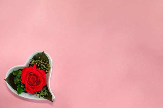 Flower red rose in a heart-shaped pot on a pink background, top view