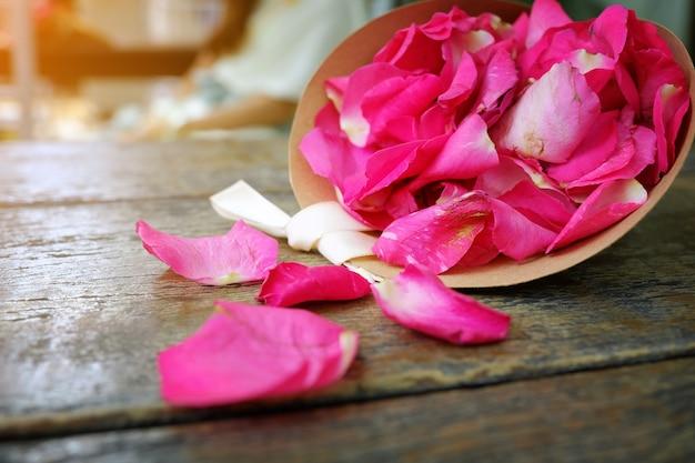 Цветочные красные лепестки роз на деревянном фоне