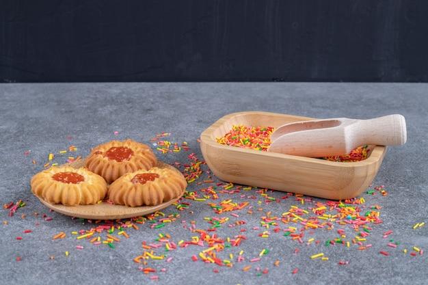 Печенье в форме цветка с разноцветной посыпкой на мраморной поверхности