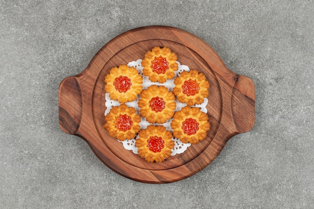 Flower shaped biscuits with jelly on wooden board