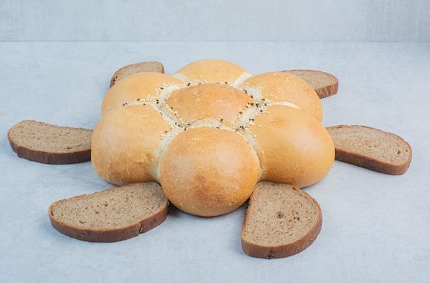 Хлеб и куски хлеба в форме цветка на белом фоне. фото высокого качества