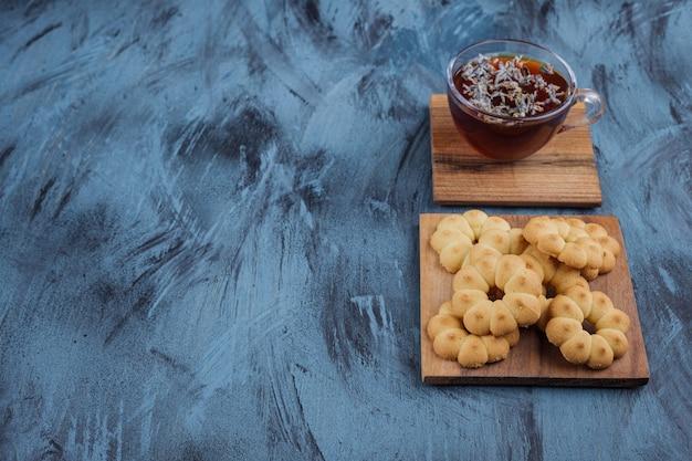 Biscotti dolci a forma di fiore e bicchiere di tisana su sfondo blu.