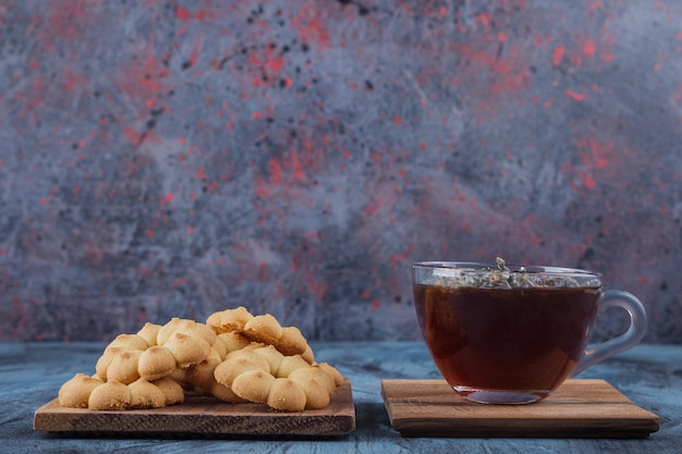 Flower shaped sweet cookies and glass of herbal tea on blue background.