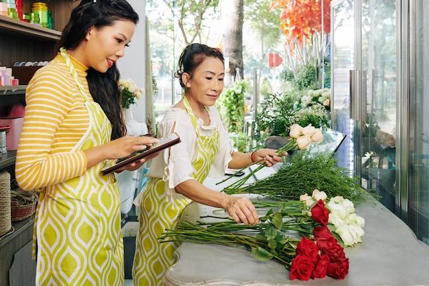 플로리스트가 고객을 위해 꽃다발을 만들 때 태블릿 컴퓨터에서 작업하는 꽃 가게 주인