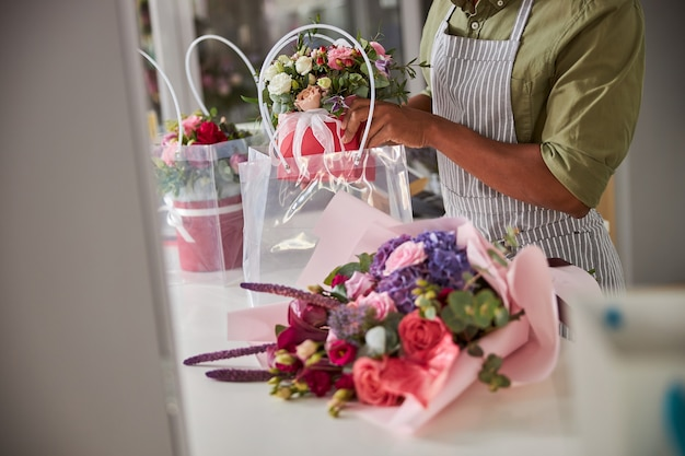 A flower shop salesperson putting a pot of blooming flowers in a plastic bag near a bouquet