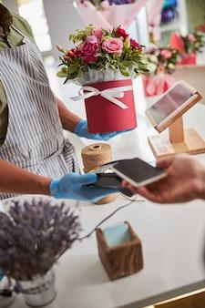 전화 결제를받는 동안 주위에 흰색 리본이 달린 꽃이 든 빨간 냄비를 보관하는 꽃 가게 직원