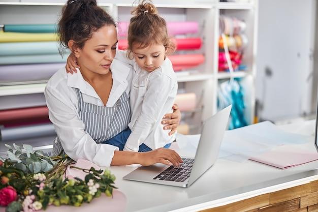 그녀의 아이와 함께 직장에서 하루를 보내는 꽃 가게 직원