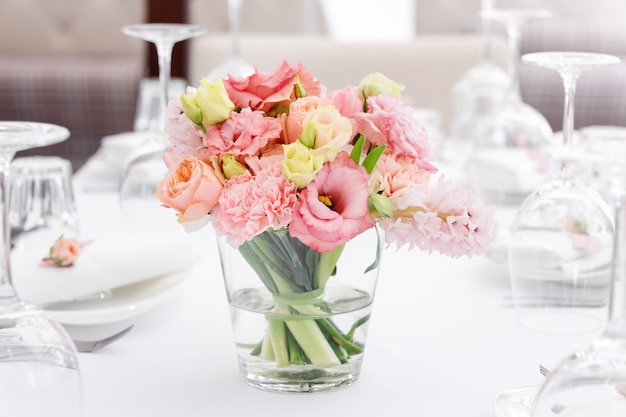 Flower table decorations for holidays and wedding dinner. table set for holiday wedding reception in outdoor restaurant.
