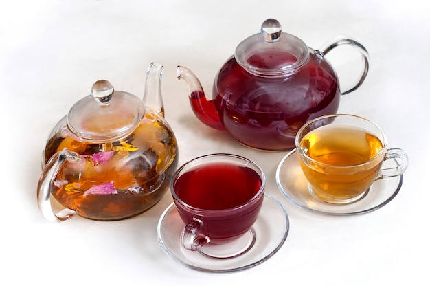 Flower tea in clear glass teapots with teacups.
