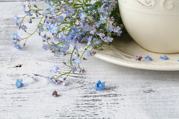 Flower tea, forget-me-nots, leaves and flowers on a wooden wall
