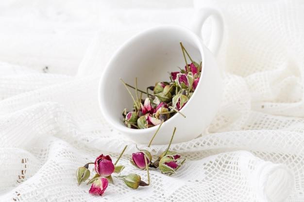 古い木製のテーブルの上の花茶バラのつぼみ