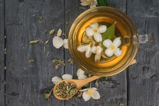 Цветочный чай с лепестками жасмина, завариваемый в стеклянной посуде. бодрящий напиток, полезный для здоровья.