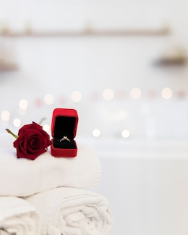 Flower, towels and ring in jewelry box near spa tub with candles