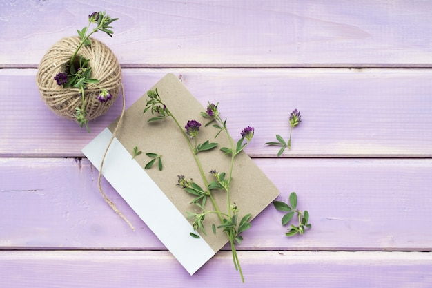 Flower twigs on closed notebook with spool of string on purple wooden backdrop