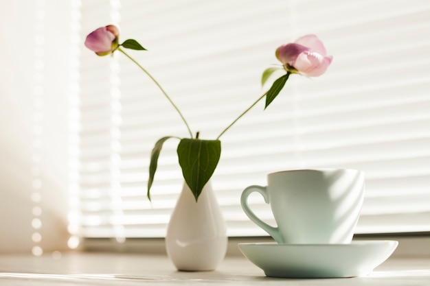 Flower vas and coffee cup with saucer near window blind