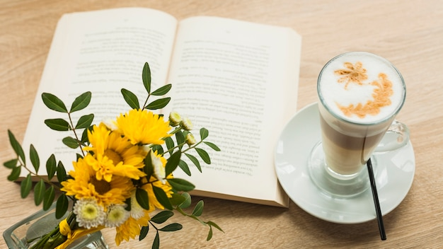 Flower vas and latte coffee cup with open book on wooden textured surface
