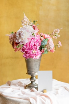 Flower vase by a card on a table