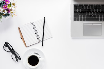Flower vase; eyeglasses; diary; pencil and coffee cup with laptop on white background