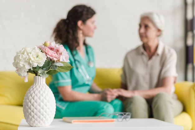 Flower vase in front of nurse and senior female patient sitting on sofa