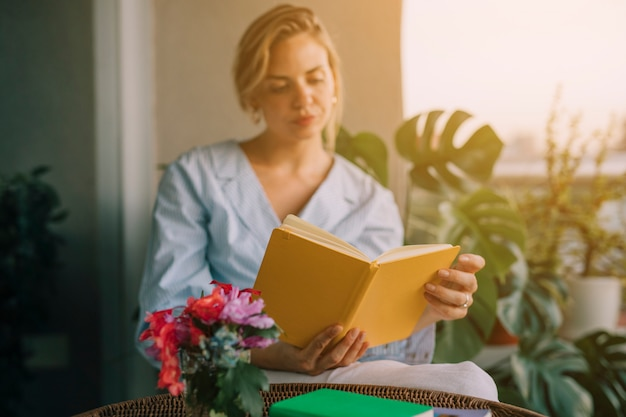 Flower vase in front of young beautiful woman reading book