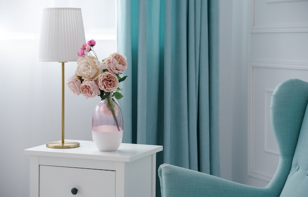Flower vase and golden table lamp with blue armchair and curtains