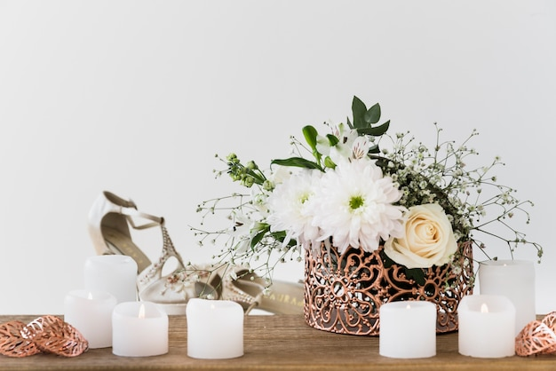 Flower vase near the burning candle and wedding shoes against white background