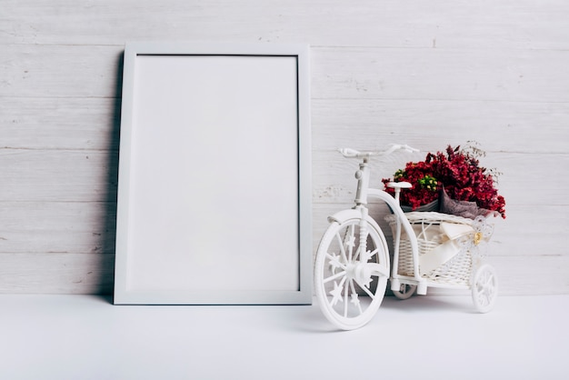 Flower vase with bicycle near the white blank frame on desk