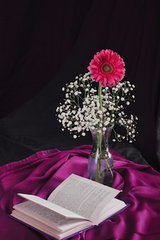 Flower with bloom twigs in vase near volume and violet textile in darkness