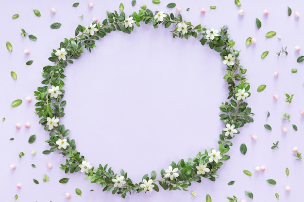 Flower wreath frame made of different flowers and leaves, flat lay, top view background