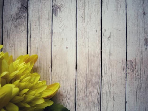 꽃 노란색 흰색 나무 테이블에 배치됩니다.