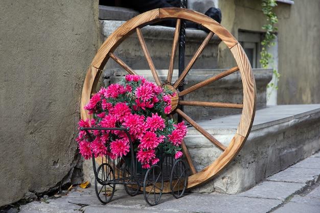 タリン通りの階段の前にアンティークの古いホイールと花の咲くワゴン。
