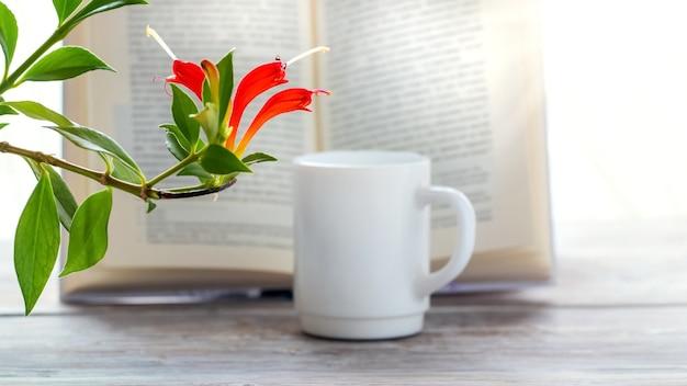 コーヒーのマグカップと開いた本の近くに開花観葉植物