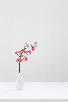 흰색 배경에 흰색 꽃병에 꽃 분홍색 벚꽃 지점