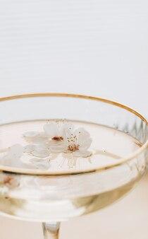 空きスペースと白い背景の上のガラスシャンパン反射純度鮮度再生の開花木