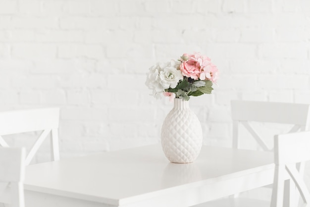 Flowering white vase on table against brick wall