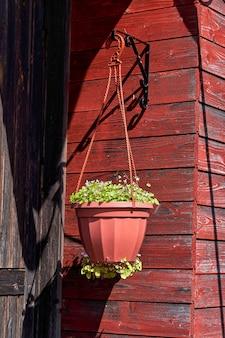 Вазон, подвешенный к деревянной стене дома