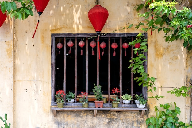 Flowerpots with flowers, yellow wall and window with red chinese lanterns in hoi an old town