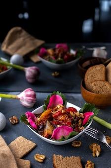 灰色の机の上の野菜と塩漬けに調理されたスライスされたチキンスライスと一緒に花