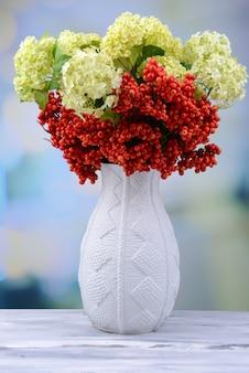 花瓶、木製のテーブル、明るい背景に花とベリー