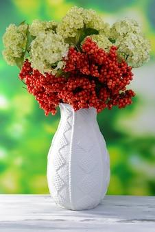 밝은 배경에 나무 테이블에 꽃병에 꽃과 열매