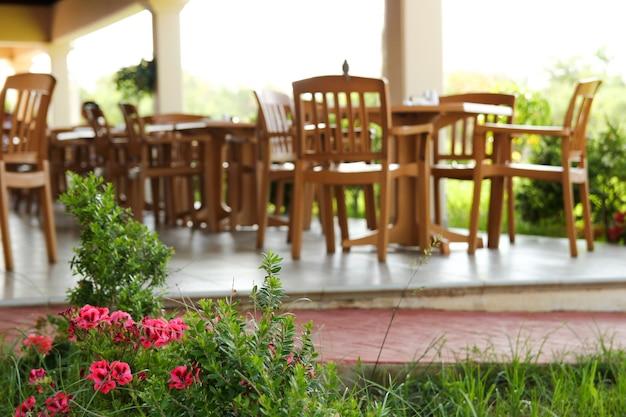 レストランテラスの外の花とぼやけたテーブルと椅子