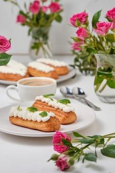 Цветы и эклеры, украшенные кремом и мятой на белом столе. десерт для романтического свидания. торты на праздник.